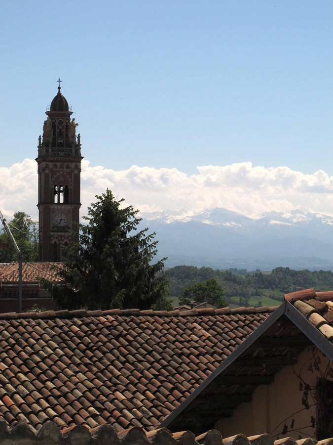Monforte d'Alba against a backdrop of clouds and mountains.